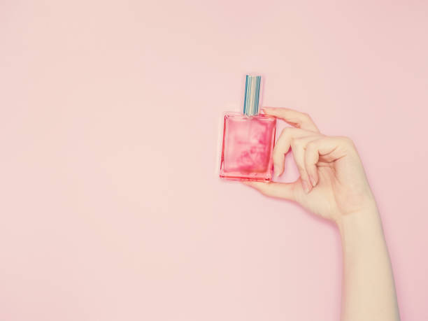 beauty for woman concept from beauty woman hand show and hold perfume bottle in hand with isolated pink pastel background - profumi foto e immagini stock
