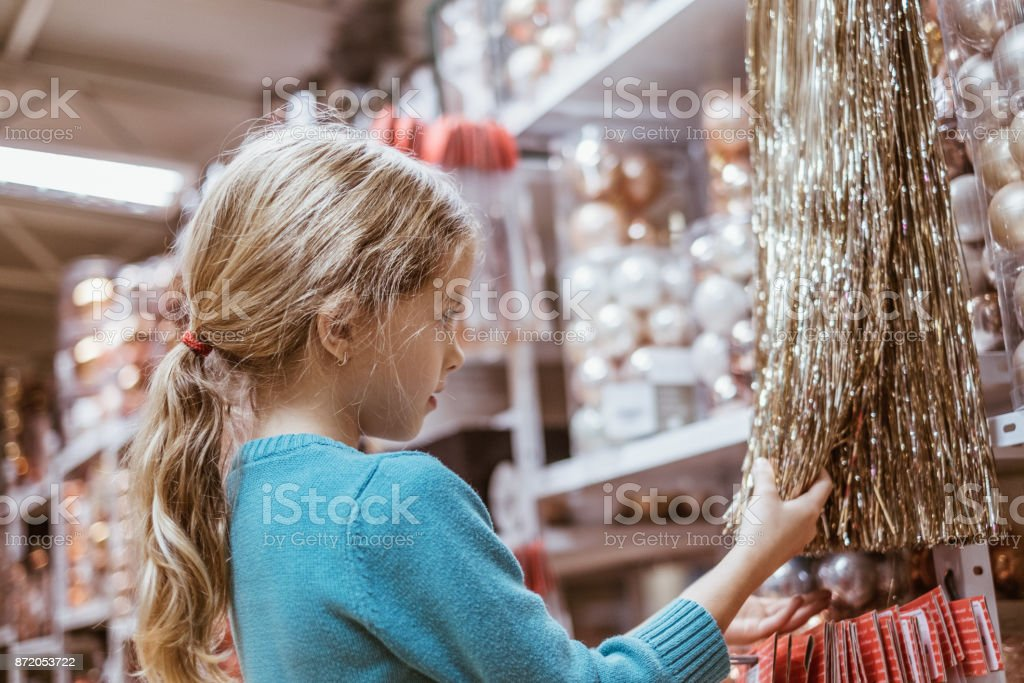 Beauty girl chosing christmas decoration in christmas store stock photo