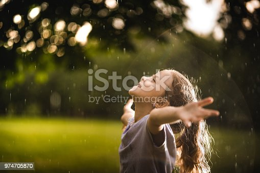 Little girl arms outstreched standing on the rain