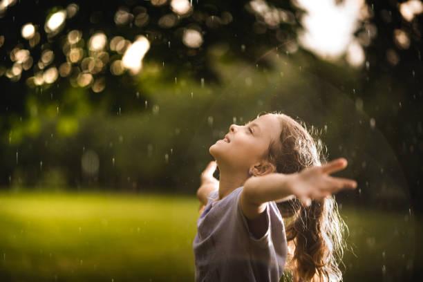 schönheit mädchen auf den regen in der natur genießen - regenzeit stock-fotos und bilder