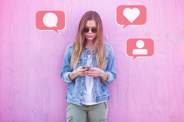 美容女孩影響者使用社交媒體在智慧手機上喜歡, 評論, 在粉紅背景周圍的追隨者圖示 - influencer 個照片及圖片檔