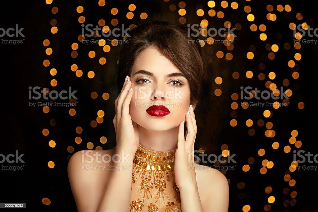 Beauty girl makeup. Fashion jewelry. Elegant lady in golden dress stock photo