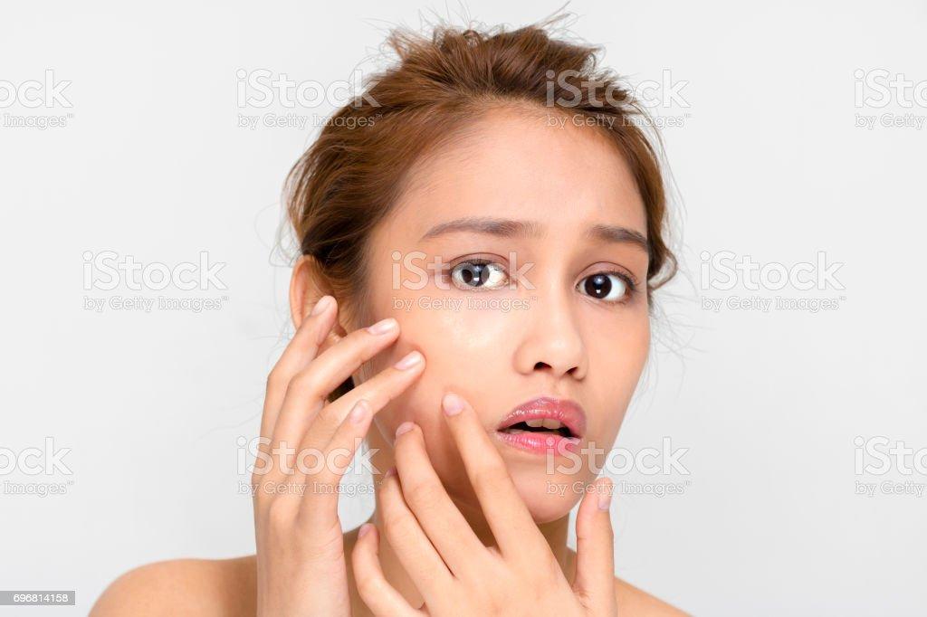 beauty girl of half latina and half asian who checks her skin, skin care, acne treatment stock photo