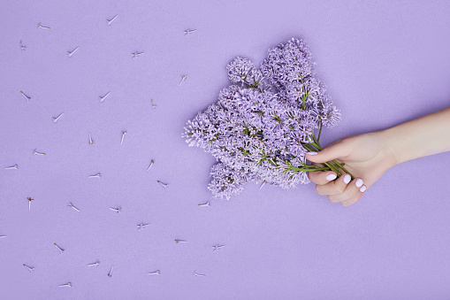 istock Beauty Hand of a woman with blue flowers lies on table, blue paper background. Natural cosmetics product and hand care, moisturizing and wrinkle reduction, skincare 1182895649