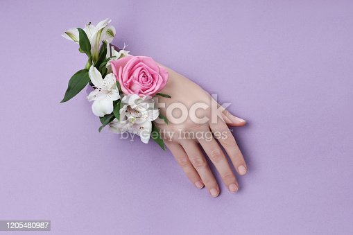 istock Beauty Hand with flowers in a hole in a purple paper background. Nature hand Cosmetics, natural flower extract, moisturizing and softening the skin 1205480987