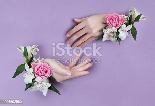 istock Beauty Hand with flowers in a hole in a purple paper background. Nature hand Cosmetics, natural flower extract, moisturizing and softening the skin 1206602560