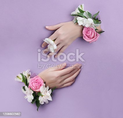 istock Beauty Hand with flowers in a hole in a purple paper background. Nature hand Cosmetics, natural flower extract, moisturizing and softening the skin 1206602562