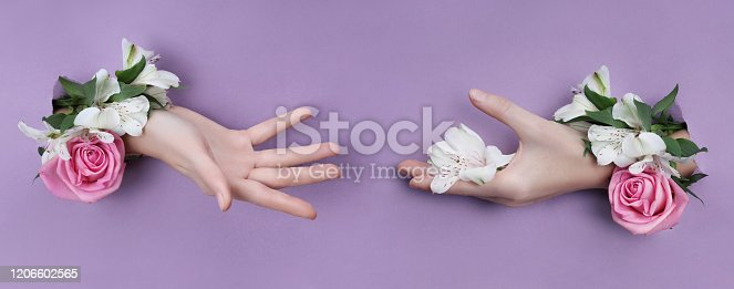 istock Beauty Hand with flowers in a hole in a purple paper background. Nature hand Cosmetics, natural flower extract, moisturizing and softening the skin 1206602565