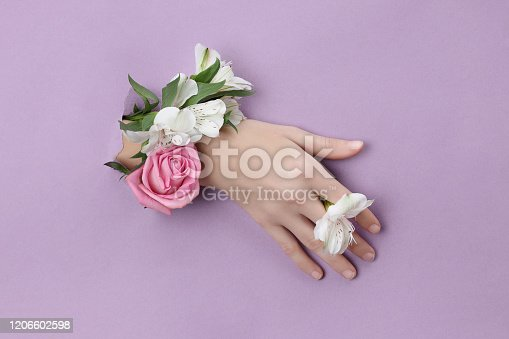 istock Beauty Hand with flowers in a hole in a purple paper background. Nature hand Cosmetics, natural flower extract, moisturizing and softening the skin 1206602598