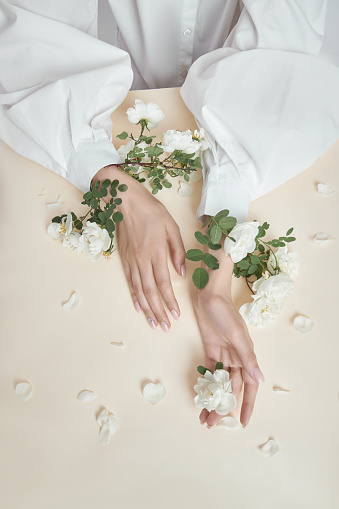 istock Beauty hands woman with rose flowers are on the table. Natural cosmetic for hand skin care. Fashion makeup 1264972498