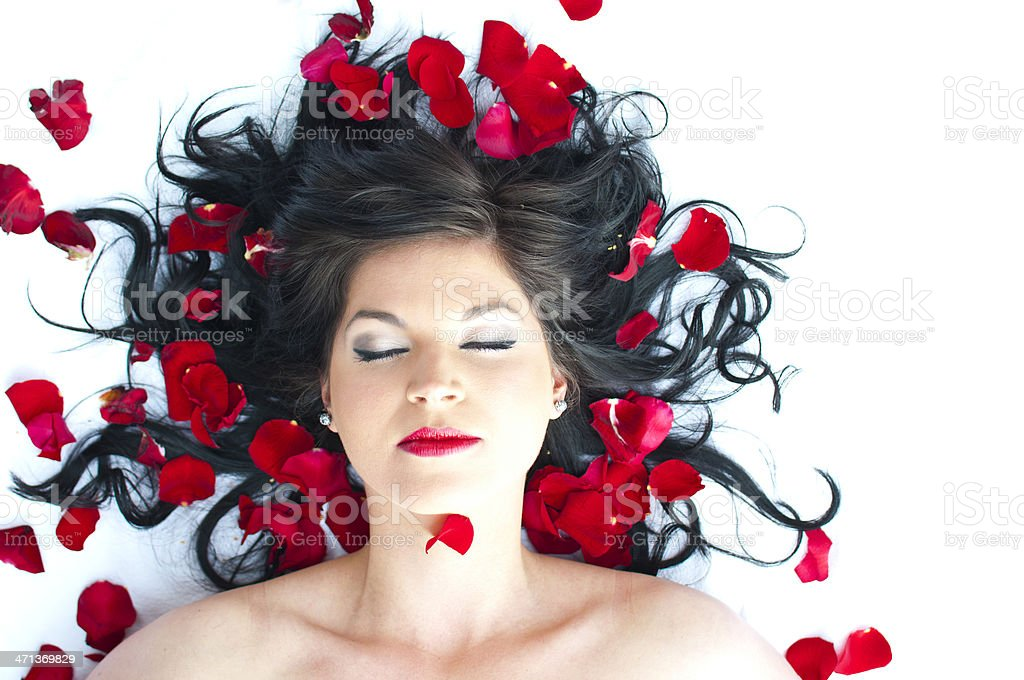 Beauty in bed of red roses stock photo