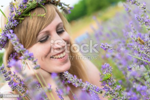 Young, attractive women in the lavender field, with wreath on her head, long blond hair. She is smilling and looking small green grasshopper on lavender plant.
