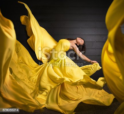 Shot of a a woman dancing surrounded by flowing yellow fabric