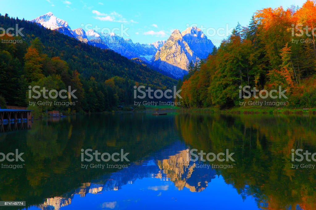 Beauty in nature: Riessersee alpine turquoise lake with reflection at gold colored sunrise, with Zugspitze, Waxenstein and Alpspitze view– dramatic Bavarian alps - Majestic alpine landscape in autumn, Snowcapped mountains – Garmisch, Bavaria, Germany stock photo