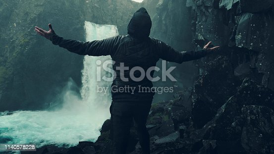 Young man enjoying waterfall. Happiness