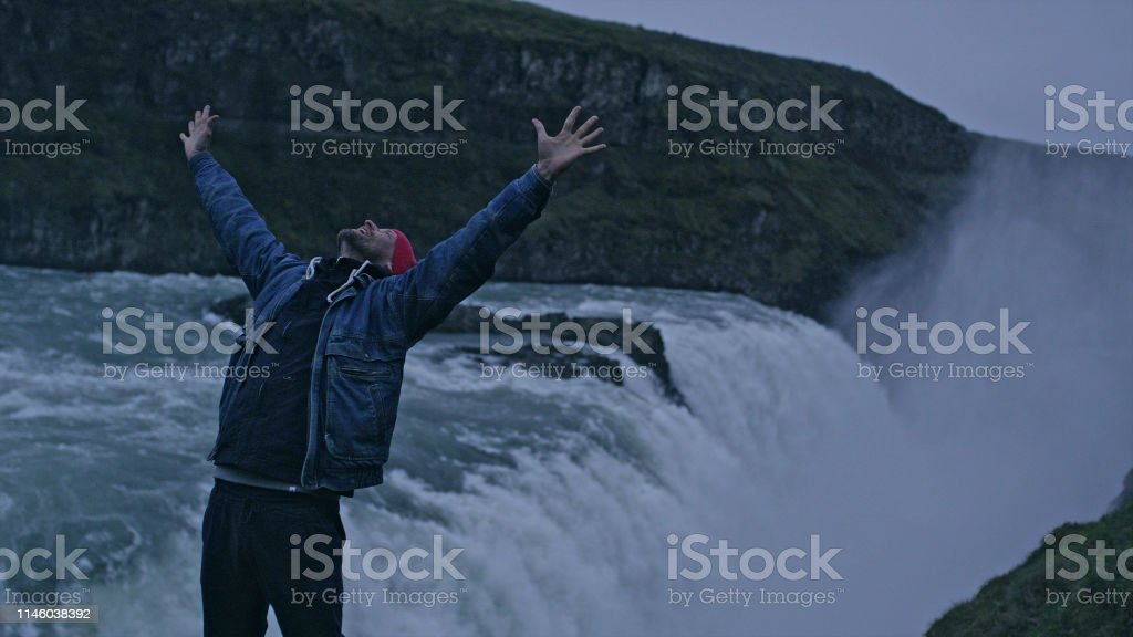 Young man enjoying waterfall. Happiness