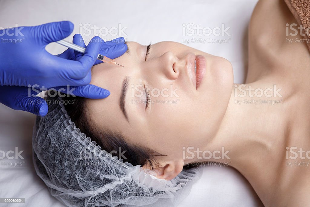 beauty injection botox face forehead needle stock photo