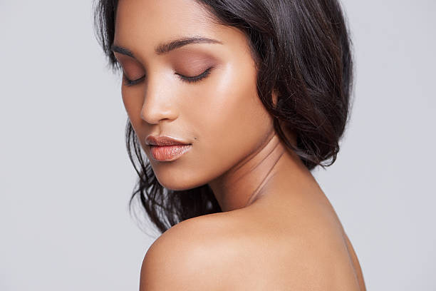 Beauty is skin deep Shot of a beautiful young woman standing with her eyes closed smooth stock pictures, royalty-free photos & images
