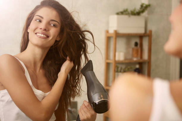 Beauty is using hairdryer stock photo