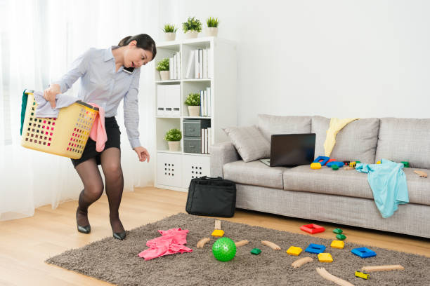 beauty lady office work using mobile smartphone attractive beauty lady office work using mobile smartphone call and talking when she back to home put mess living room in order. kids cleaning up toys stock pictures, royalty-free photos & images