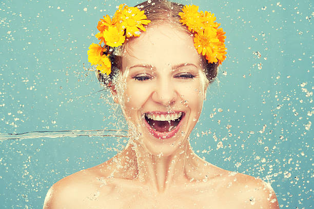schönheit lachen mädchen mit akzenten von wasser und gelbe blumen - blumen make up stock-fotos und bilder