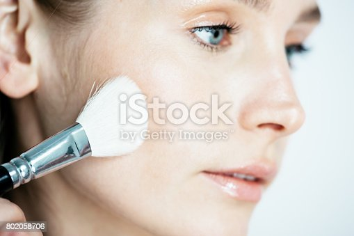 istock Beauty makeup  woman smiling closeup. Beautiful young woman applying foundation powder or blush with makeup brush. Isolated on white background. 802058706