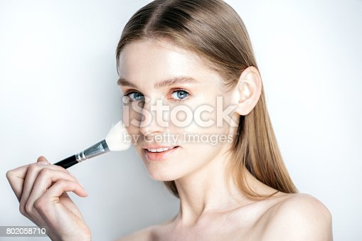 istock Beauty makeup  woman smiling closeup. Beautiful young woman applying foundation powder or blush with makeup brush. Isolated on white background. 802058710
