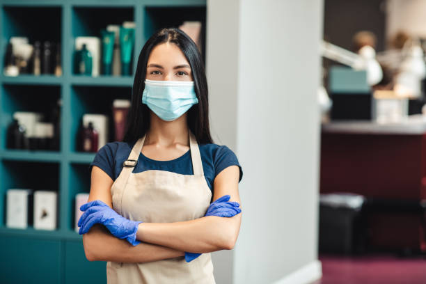 Beauty master in protective mask and gloves standing at hairdresser's interior, empty space stock photo