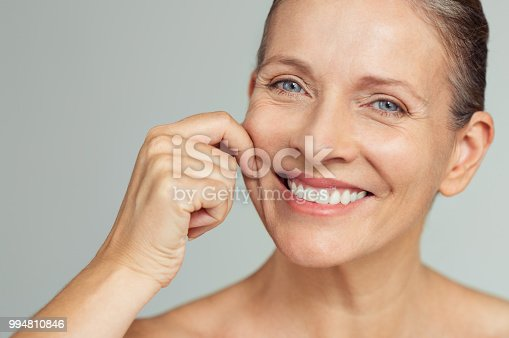 Senior woman pulling cheeks to feel softness and looking at camera. Beauty portrait of happy mature woman smiling with hands on cheek isolated over grey background. Aging process and perfect skin concept.