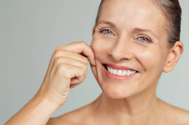 Beauty mature woman pulling perfect skin Senior woman pulling cheeks to feel softness and looking at camera. Beauty portrait of happy mature woman smiling with hands on cheek isolated over grey background. Aging process and perfect skin concept. human skin stock pictures, royalty-free photos & images