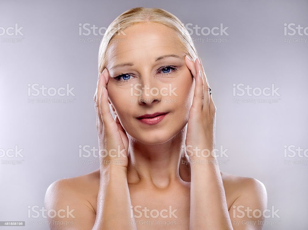 Beauty mature woman tightening a face with her hands. stock photo