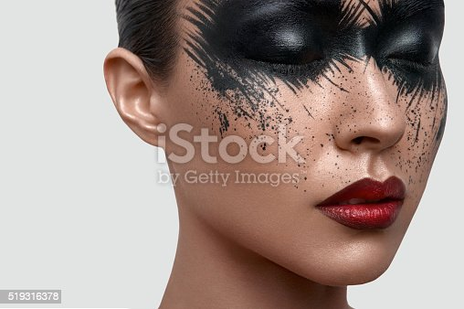 istock Beauty Model with black Paint Stains on Face 519316378