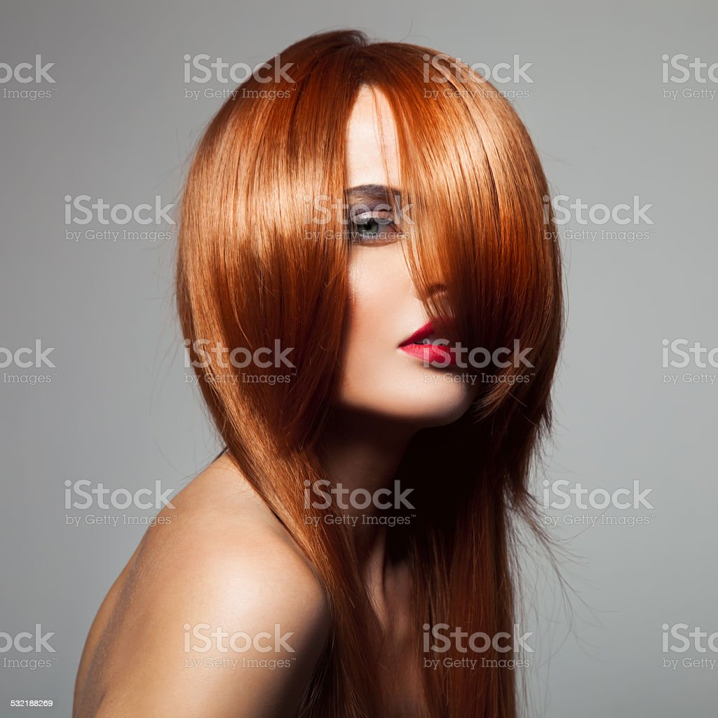 Beauty model with perfect long glossy red hair. Close-up portrai stock photo