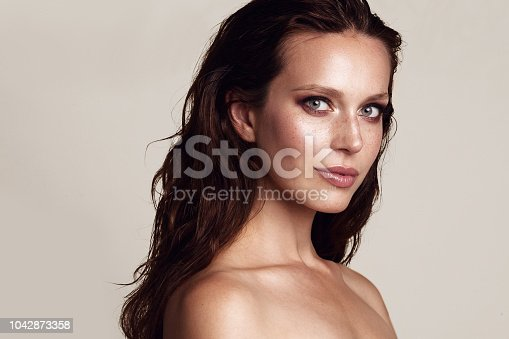 Beauty woman portrait. Beautiful model girl with perfect fresh clean skin and smoky eyes makeup. Youth and skin care concept. Beige background.