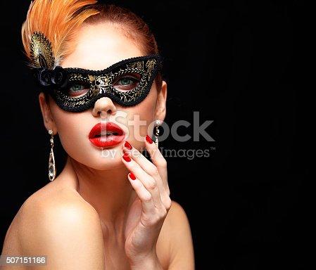 istock Beauty model woman wearing venetian masquerade carnival mask at party 507151166