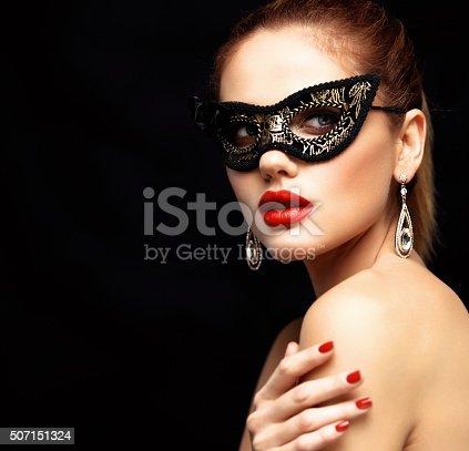 istock Beauty model woman wearing venetian masquerade carnival mask at party 507151324