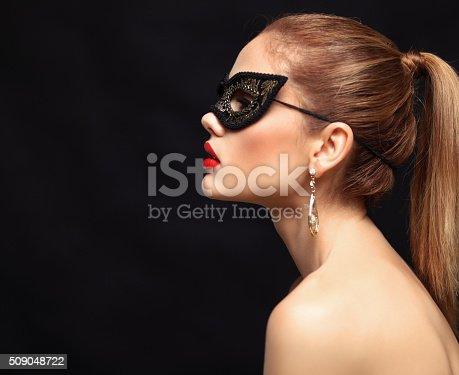 istock Beauty model woman wearing venetian masquerade carnival mask at party 509048722