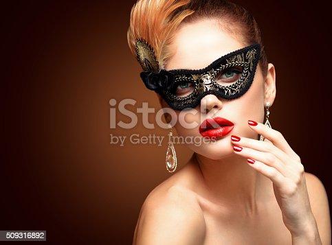 istock Beauty model woman wearing venetian masquerade carnival mask at party 509316892