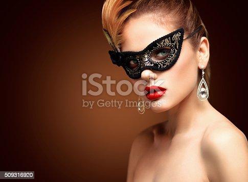 istock Beauty model woman wearing venetian masquerade carnival mask at party 509316920