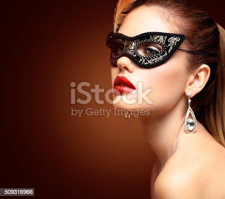 istock Beauty model woman wearing venetian masquerade carnival mask at party 509316966