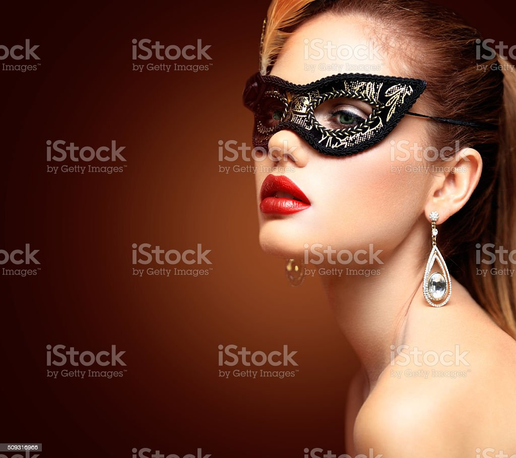 Beauty model woman wearing venetian masquerade carnival mask at party stock photo