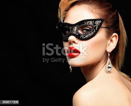 istock Beauty model woman wearing venetian masquerade carnival mask at party 509317008