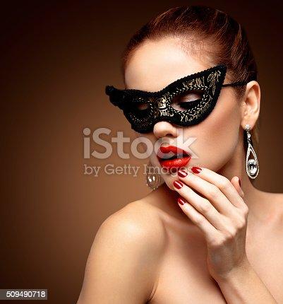 istock Beauty model woman wearing venetian masquerade carnival mask at party 509490718