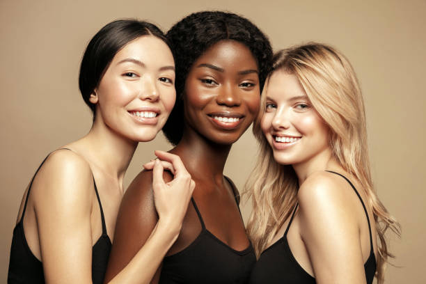 beauty. multi ethnic group of womans with diffrent types of skin  together and looking on camera. diverse ethnicity women - caucasian, african and asian posing and smiling against beige background. - contrasti foto e immagini stock