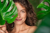 istock Beauty natural woman covering her face with tropical leaf 1289221022