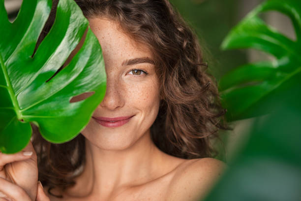 Beauty natural woman covering her face with tropical leaf stock photo