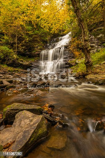 Autumn waterfall scenery with fallen leaves and beautiful fall colors at Ricketts Glen Park in Pennsylvania