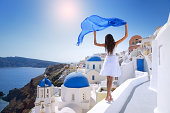 Beautiful Woman in a white dress dancing over the rooftops in front of the famous Town Oia on Santorini, Greece.