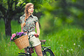 Portrait of a young beautiful woman on a vintage bicycle.