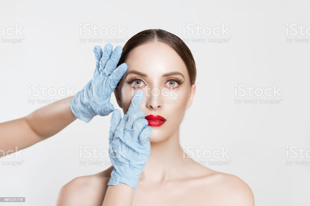 Beauty, people and health concept. beautiful young woman getting ready for eyelid lift, blepharoplasty plastic surgery doctors's hands in blue gloves pointing fingers to her eye over white background. – Foto